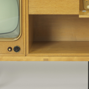 Rectilinear cabinet of light wood on three dark openwork supports; the form composed of a slat bench with two cabinets featuring television on left, one pull-out drawer holding phonograph and drop-front door concealing radio above record storage area in center section, and speaker cabinet on right, with circular speaker.