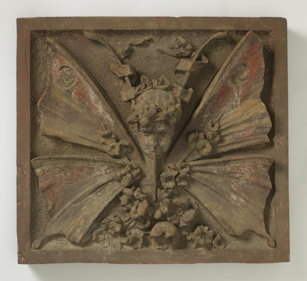 A square tile with flat border. At center, a head with antennae and butterfly wings. Flowers at bottom. Traces of polychrome decoration.