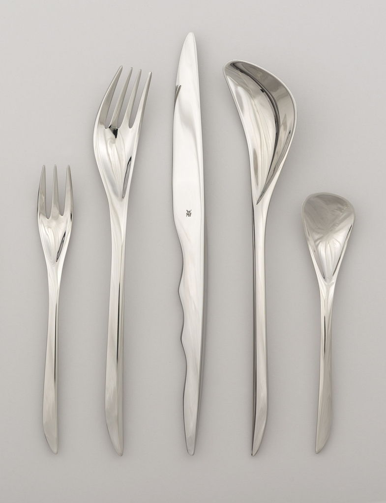 Five-piece flatware place setting, each piece an assymetrical form of polished metal: three-tined small fork (-8) with countoured tapered handle; four-tined dinner fork (-9) curved slightly to the right with long countoured tapered handle; dinner knife (-10) with attenuated ovoid blade transitioning to handle ridged on one side; tablespoon (-11) with deep bowl curved to left and long contoured tapered handle; teaspoon (-12) with roughly triangular bowl and tapered handle.