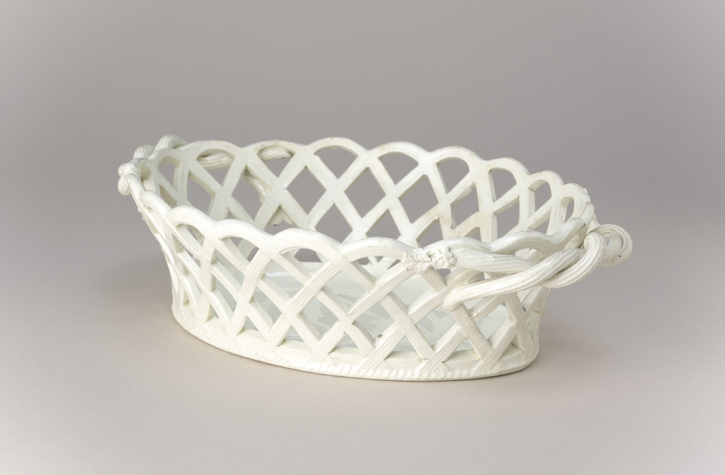 A white earthenware basket with woven handles. Mold marks visible, and marks of supports in kiln.
