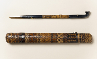 Pipe (-16a) comprising bamboo stem with mouthpiece and head of blackened and partly gilt metal. Long oval two-part case (-16b,c) of reeded bamboo, sections carved and stained in three different patterns simulating basket weave; metal ring and rim.
