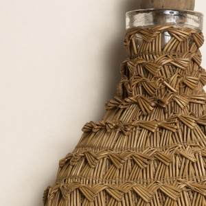 Flat, oval glass flask covered in woven straw; conical cork stopper.