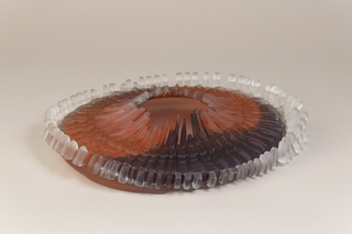 Glass disc-like bowl composed of ribs resembling a fan belt with a hole in the center, in black and brown.