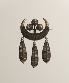 """Brooch consisting of a wide """"U"""" shaped piece made out of woven brown hair capped at the ends with gold. Within the """"U"""" shape are three balls of woven hair; hanging from the """"U"""" are three teardrop shaped pendants of woven brown hair, accented with gold hardware."""