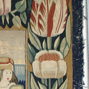 Pillow cover showing a crudely-rendered scene. Two women, each holding a jug, a man on horseback and another standing behind him. Landscape in background and a floral border.