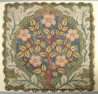 Design of flowering rose stem surrounded by wreath of oak leaves. Finished on all four sides with fringe in colors used in the embroidery.