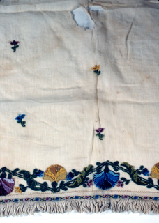 Rectangular white cotton length hemstitched and fringed on all fours sides. Narrow border design of tiny flowers in blue, pink and green beads. Two short ends have design of stylized blossoming vine in red, blue, yellow and green. Tiny flowers scattered over ground.