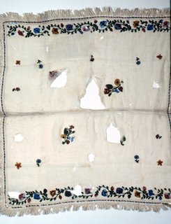 Square white cotton textile made of two pieces stitched together with lace stitches. Fringed on all four sides. Flowers scattered over ground. Two ends trimmed with flowering vine design. Polychrome beads used.