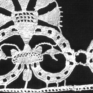 Fragment of a border with flowerheads, probably carnations, supported by scrolling forms.