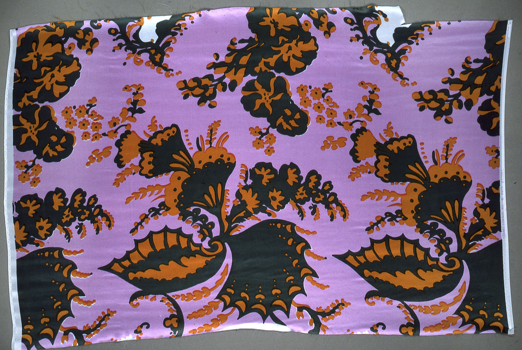 """Fragment printed in pink, green and orange. Pattern shows large scale swirling """"bizarre"""" design of wings and floral elements."""