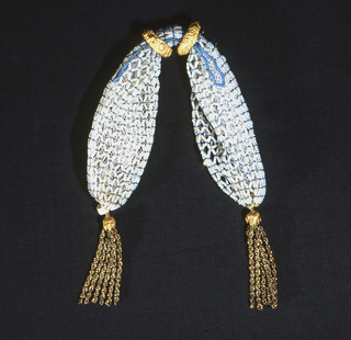 An open mesh formed of small opalescent beads with a turquoise bead at each intersection and turquoise beads outlining the side opening. Two floral patterned gold rings control slit opening. Twisted gold and cut metal beads form tassels at either end.