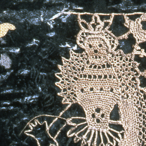 Small piece of unfinished work showing the manner in which punto in aria needle laces are made. Standing female court figure outlined and half-filled, on dark green paper.