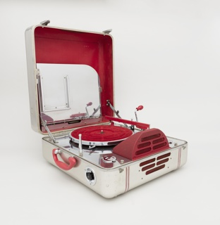 Portable phonography in square aluminum case with rounded edges and corners; red plastic handle and control dials; one side with pierced slits for speaker. Bottom of case contains metal deck with red turntable, needle arm, domed speaker and controls. Lid with file holder with sheet metal dividers to house records.