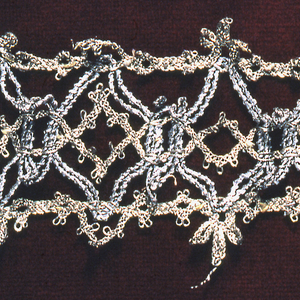 Gold and silver metallic lace in a straight band of interlocking diamond shapes, with an elaborate picot on both long edges.