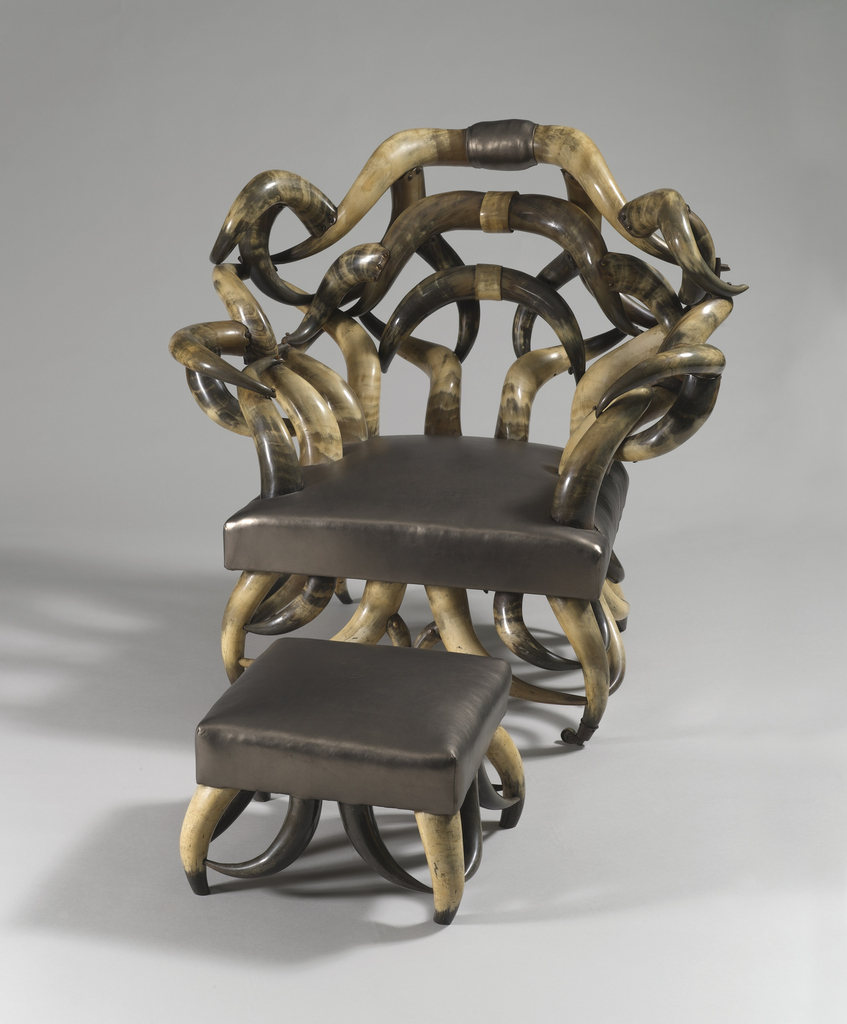 Bow-shaped joined crest rail above similarly shaped shoulders, over a back support of twisting horns.  Similarly composed arm supports, centering a leather upholstered seat on four twisting cow-horn legs terminating in brass claw-and-glass ball feet.  The front feet enclose opposing twisting horn returns. Part of group with ottoman 1986-39-2.
