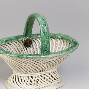 This basket and tray are glazed earthenware but are made in the style of wicker ware. The ten-sided tray is circular with scalloped edges. The sides have varying loose cross hatched pattern while the center bottom consists of a tight cross hatched pattern with a row of green leaves around the border of the bottom piece. There are also leaves repeated, one in between each section of the ten sides. The matching basket has the same construction, including the cross-hatched wicker style. However, the basket sits upon an attached foot and has the leaf green color around the top edge of the basket and handle.