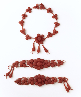 A red colored necklace made of weaved balls in threes, with a centered flower, dangling three tear drop shapes. Bracelets are red colored and made of weaved balls, with a centered flower, dangling two tear drop shapes at the end.