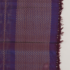 A bright violet ground with an iridescent quality created by using magenta warps and bright blue wefts, with wide pattern bands of zigzags and geometric forms in shiny golden rayon yarns. Fringed at both ends.