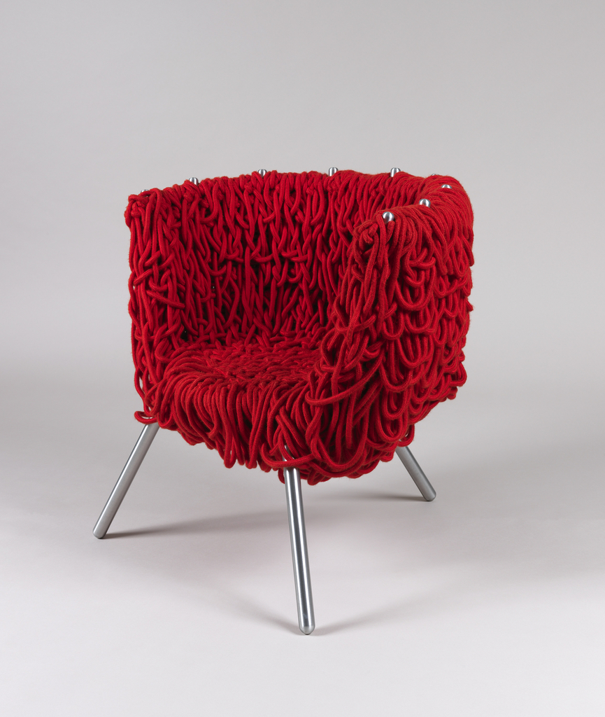 Three-legged bucket-type chair, the arms/back/seat formed by a steel frame 'upholstered' in red cotton rope woven and looped throughout interstices of frame.