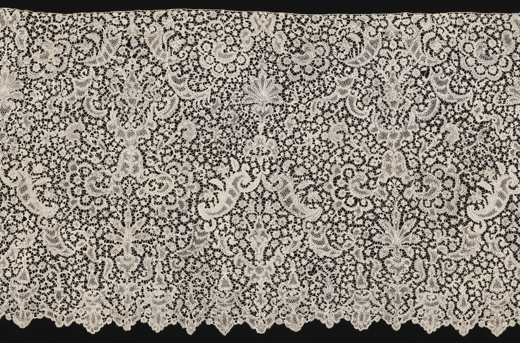 Brussels-style flounce patterned by two alternating vertically symmetrical groupings of scrolls and plants.