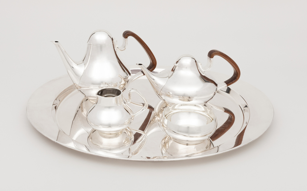 Set consisting of gourd-shaped coffee pot and shorter teapot, each with contoured conical spout, hinged domed lid, and angled walnut and silver handle; short gourd-shaped silver creamer, and low, circular silver sugar bowl, all on a simple, oval, broad-rimmed silver tray.