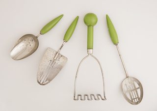Wedge-shaped chrome-plated steel form, the center pierced with slots, on short L-shaped steel wire neck attached to long ovoid handle painted light green.