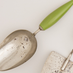 Broad chrome-plated metal spoon, pierced with drainage slots, on steel wire neck attached to long ovoid handle painted light green.