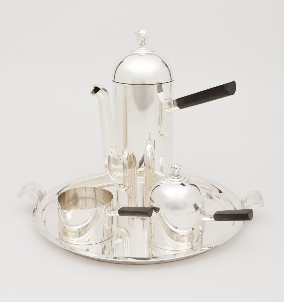 Straight-sided cylindrical coffee pot  and creamer, the former with domed lid, the covered sugar bowl of bulbous cylindrical form,   the handles of the pot, creamer and sugar bowl of ebony set at right angles to the body of the pieces,