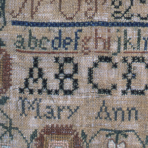 Multiple bands of alphabets separated by narrow borders, with a wide floral border of carnations and tulips, embroidered in colored silks on a coarse natural linen ground.