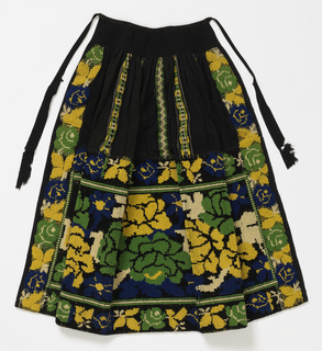 Apron made from a panel of fabric patterned with a strip of bold flowers and narrow, widely spaced bands of blue, green, white, and yellow on black.