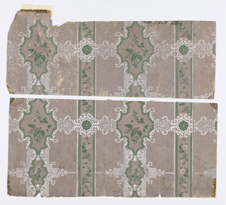 White scroll pattern forming cartouches framing green and pink flowers traveling horizontally across vertical ribbon stripes of green and pink flowers bordered by green ribbing.