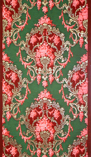Large-scale scrolling foliate and floral medallions. Medallions are dripping with foliate swags and roses. Printed in green, red, pink and white on red ground.