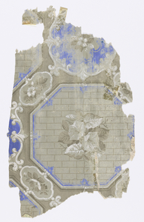 Large octagons containing gray and white morning glories against gray background, set within strong blue, white and dark gray border, alternating with cartouche containing gray and white flowers, gray background.