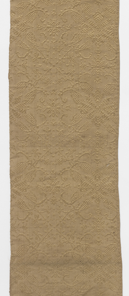 Tan silk with supplementary weft of the same color forming a design of lozenges. At intersection of lozenges are large floral motifs. Smaller, similar motifs appear in the center of the lozenges. One selvedge present.