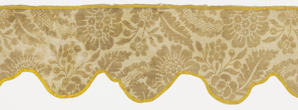 Valance with scalloped edges made of printed linen with a large scale floral pattern in brown. Bound with a yellow silk ribbon.