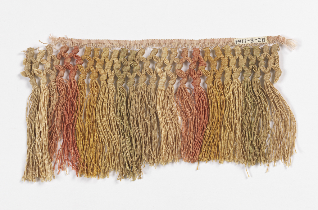 Woven heading with knotted tassels arranged in stripes of pink, yellow, cream and pale green.
