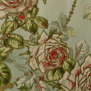 Flitter frieze with garlands of cabbage roses, rosebuds, and leaves, supported by swags of large and small beaded strings joined by fleur-de-lys. Flowers and foliage are outlined in gold mica flakes, as are the bead swags. Bands running along top and bottom edges. Printed in mauve, red, pink, shades of green and gold mica flakes on a background that shades from tan to pale blue.