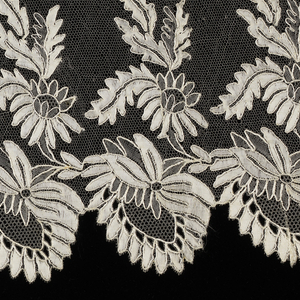 Blonde sleeve flounce in a design of deep scallops along the bottom edge. Above scallops is a horizontal vine with foliage and blossoms.
