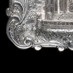 A silver card case with a castle on the front. Around the castle is decorated in a carved scroll design.