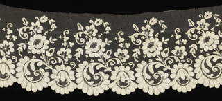 Flounce showing a pattern of flowers and scrolling leaves that form a scalloped border.