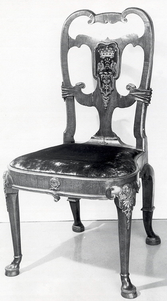 Shaped open back with voluted top rail and two horizontal crossing members enclosing a verre églomisé panel bearing the arms of the Earl of Scarsdale (extinct 1735).  Cabriole sharply raking rear legs, voluted at knees, and with moulded ankles and Dutch feet.  Voluted cabriole front legs with gilded pewter mounts at knees; hoof feet.  Gilded  pewter mask in center of front seat rail.  Slip seat.