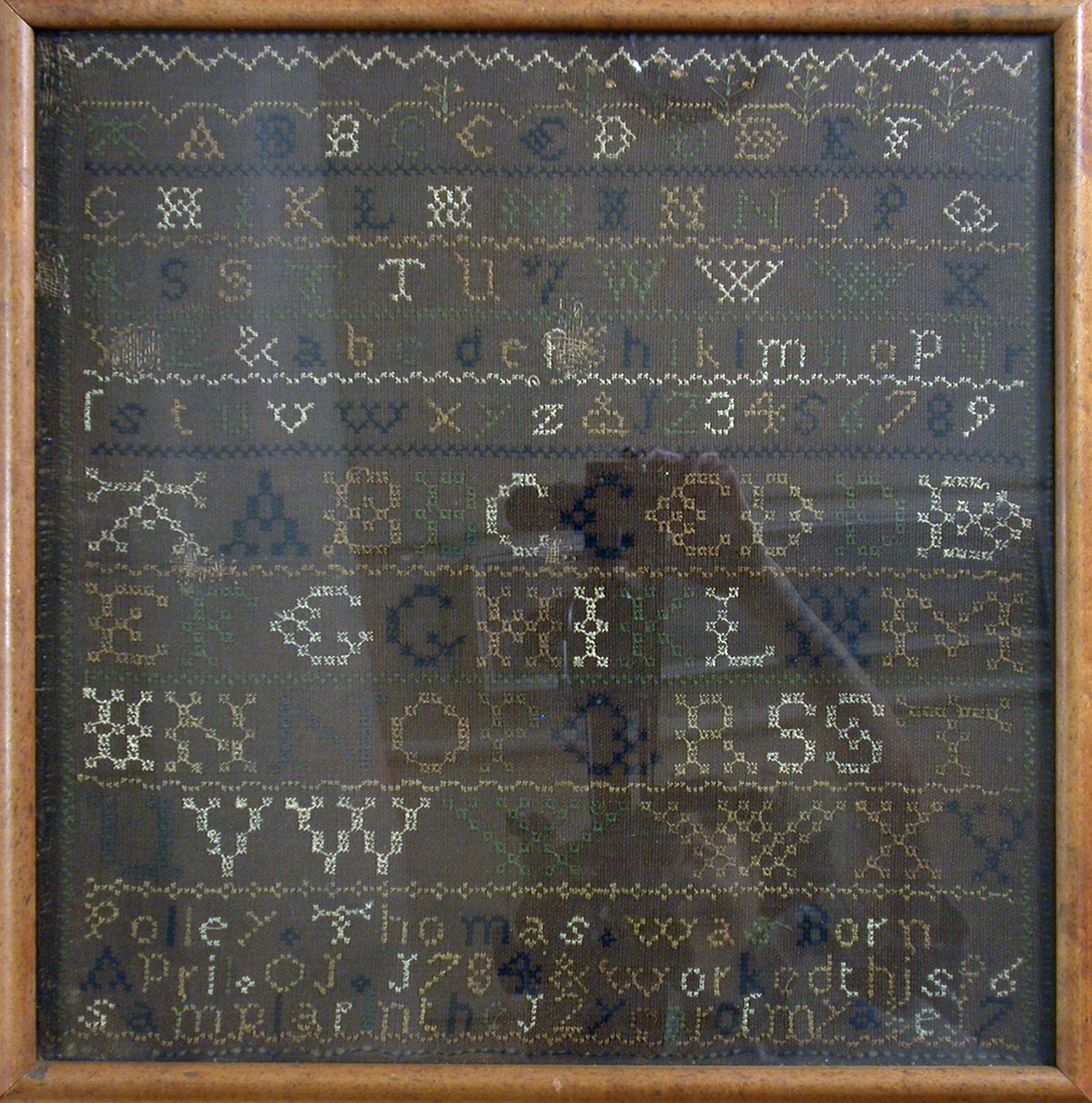 Bands of alphabets worked in several colors on a coarse brown ground, with the inscription: Polley Thomas was born April 01 1784 and worked this sampler in the 12 year of my age 1796