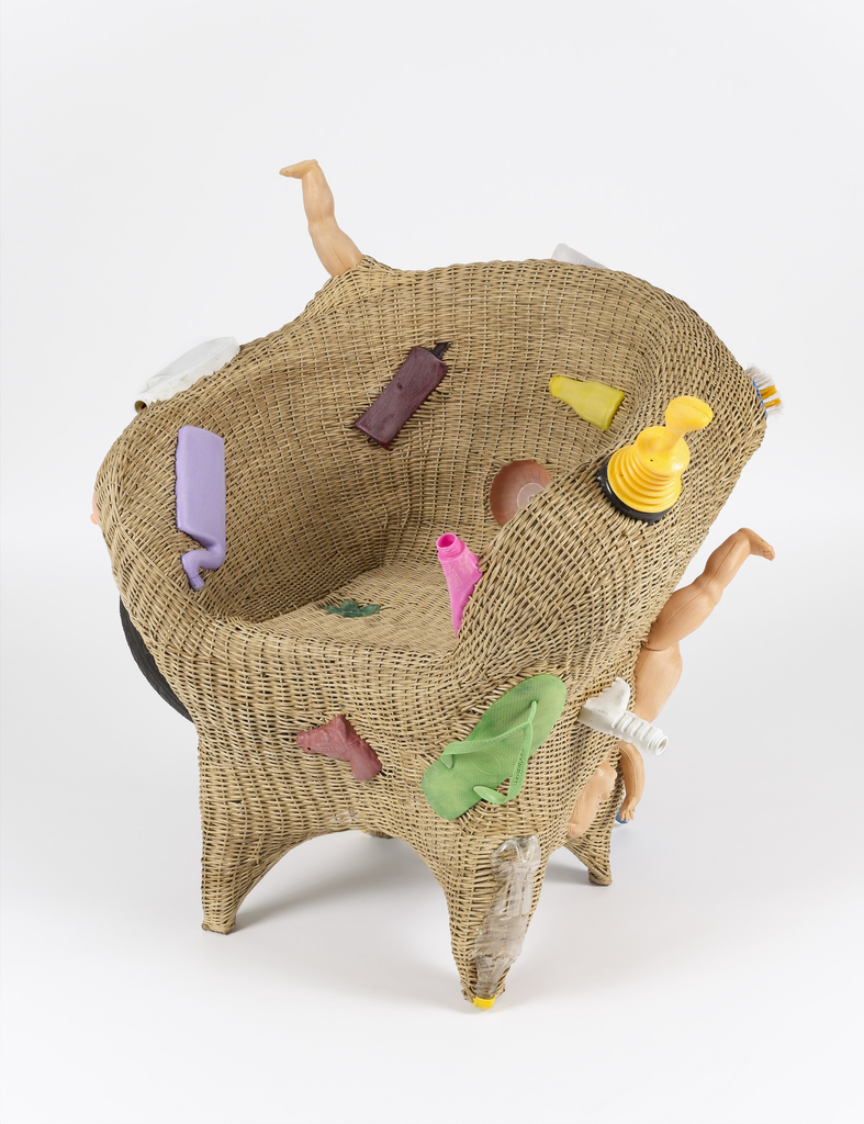 Woven tan wicker armchair with colorful found plastic and rubber objects (including discarded bottles, tire, flip-flop, broken doll parts) woven into, and protruding from, the form.