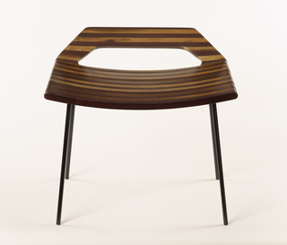 Curving rectangular seat having low, slightly upturned back with angled sides and large central opening; constructed of long laminated strips of Brazilian hardwoods in tones of dark to medium brown; mounted on black, slim cylindrical metal frame with four splayed legs.