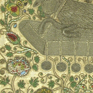 Worked predominantly in silver gilt wrapped silk core thread, with glass beads in blue, green, yellow, red and white, on a silk ground.  The Lamb of God worked in raised laid-and-couched silver thread embroidery, on a field with beadwork flowers, vines, clusters of grapes, birds.