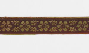 Fragments of upholstery fabric in reddish-brown with isolated motifs in dull yellow. Motifs consist of rosettes, palmettes, and leafy arabesques.