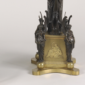 A standing female figure of patinated bronze supporting branched gilt-bronze candle arms in the form of winged female figures; the branches surmounted by a patinated putto/faun standing on a column and holding an urn-shaped bobeche; the square, gilt-bronze base with a scene of Ganymede(?) and the eagle, a patinated winged female term stands at each corner; the whole on a shaped gilt-bronze plinth.