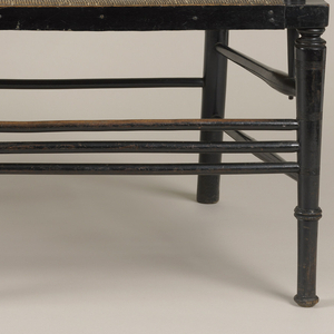 Ebonized beech bench with turned back sections, supports, and legs.  Rush seat set into frame.