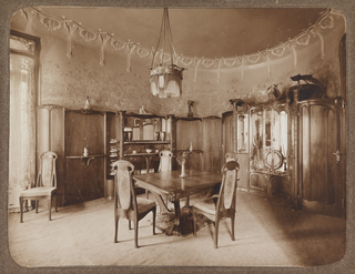 Interior view of Hector Guimard's house at 22 rue Mozart.  A square table with four chairs is in the center of the room, with built-in china closet and sideboard. Paneling on the walls about half the height of the room and ornamental plasterwork above that and on ceiling. A window with Guimard-designed lace curtain is at left.