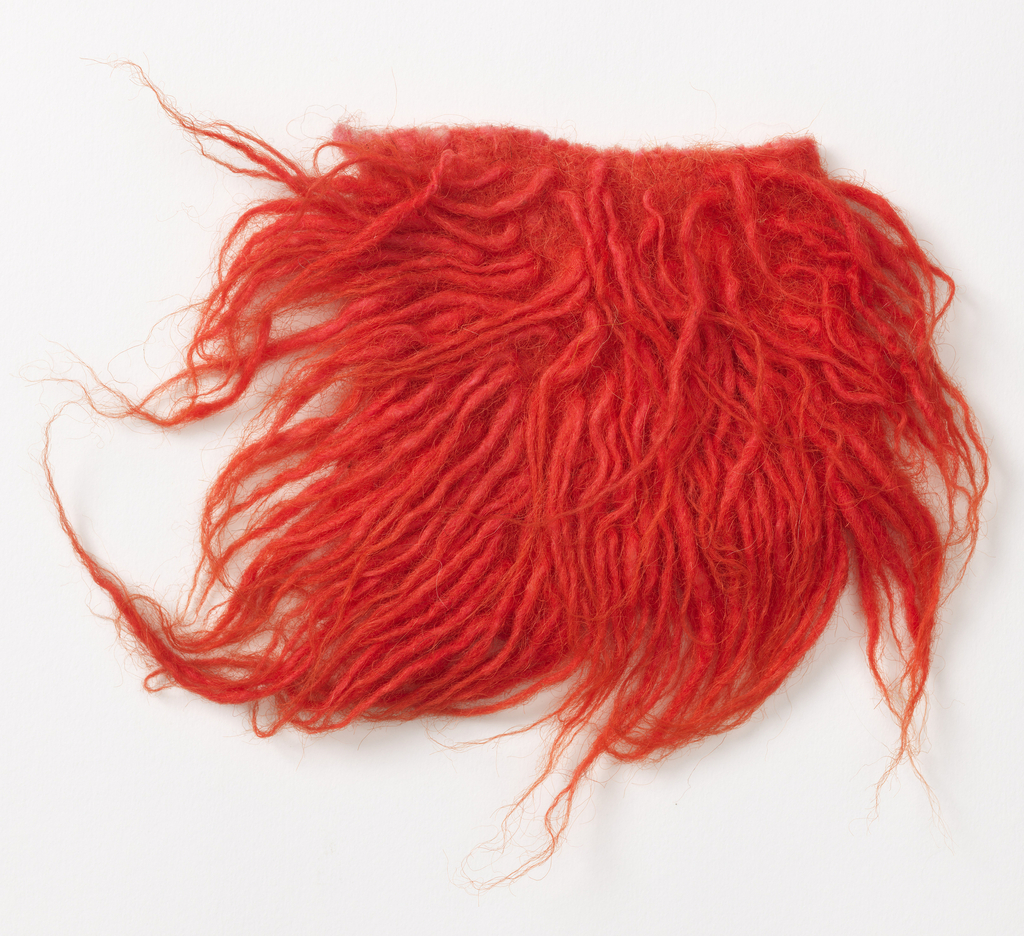 Shag rug sample known as flokati in pinkish-orange.